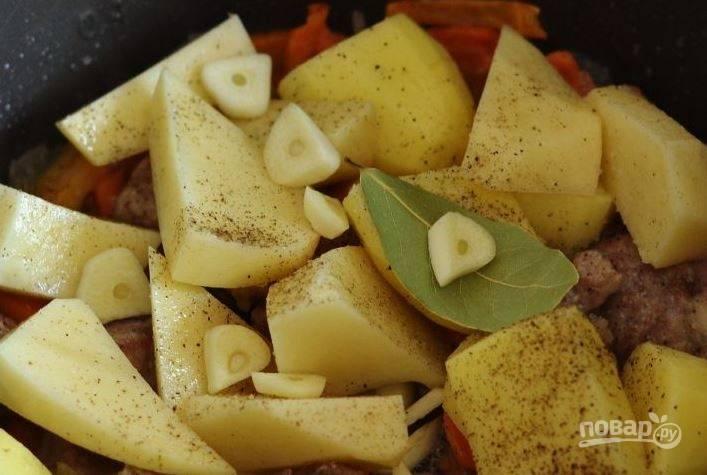 Выложите картофель к остальным ингредиентам в чашу мультиварки. Добавьте очищенные зубчики чеснока, лаврушку, посолите и поперчите.