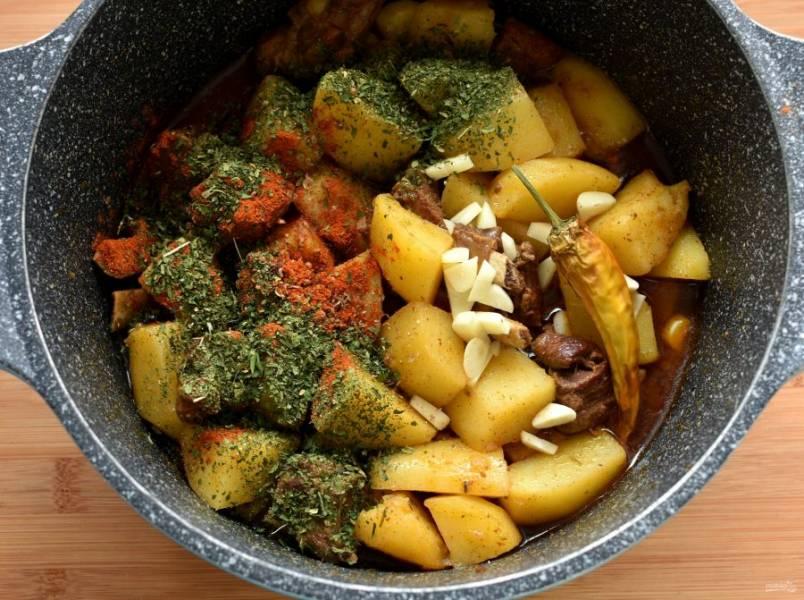 Когда картофель почти готов, наступает время второй закладки пряностей. Добавьте в каурдак крупно нарезанный чеснок, острый красный молотый перец, немного паприки и свежетолченого кориандра. Также посыпьте блюдо сухой зеленью кинзы. Если вы любитель острого, добавьте еще целый стручок перца. Хорошо перемешайте блюдо, прогрейте пару минут и отключите огонь. Плотно накройте крышкой и дайте настояться минут 20.