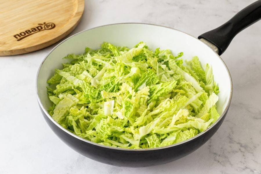 Разогрейте сковороду на среднем огне с растительным маслом. Обжарьте капусту 5 минут, чтобы она немного осела и смягчилась.