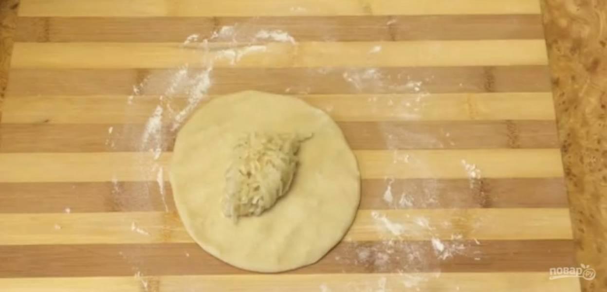 6.  Из каждого шарика вручную сформируйте тонкую лепешку. На средину выложите начинку и соберите края теста так, чтобы получился узелок. Переверните лепешку узелком вниз и вручную раскатайте в тонкий пласт.