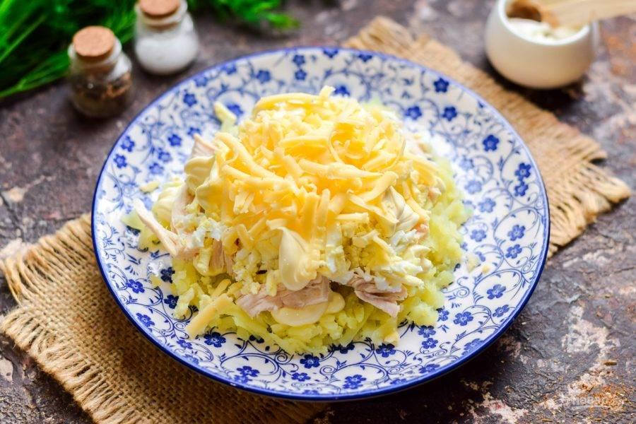 Твердый сыр натрите на средней терке, посыпьте сыром слой яиц.