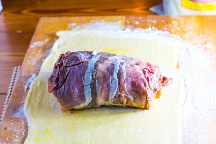 10.Смажьте пласт теста яйцом, затем достаньте мясо из холодильника и уберите пленку, поместите его в центре, заверните края к центру.