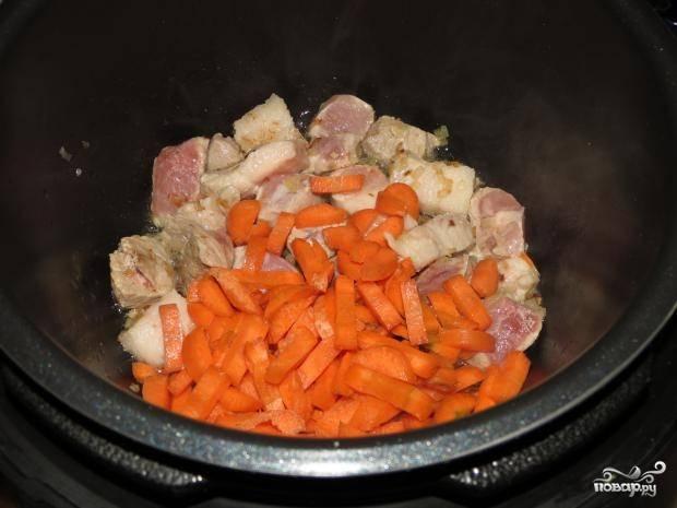 """Мясо помойте и нарежьте небольшими кусочками. Морковь почистите, помойте и нарежьте брусочками. Лук почистите и нашинкуйте. Обжарьте эти ингредиенты в скороварке в масле на режиме """"Жарка""""."""