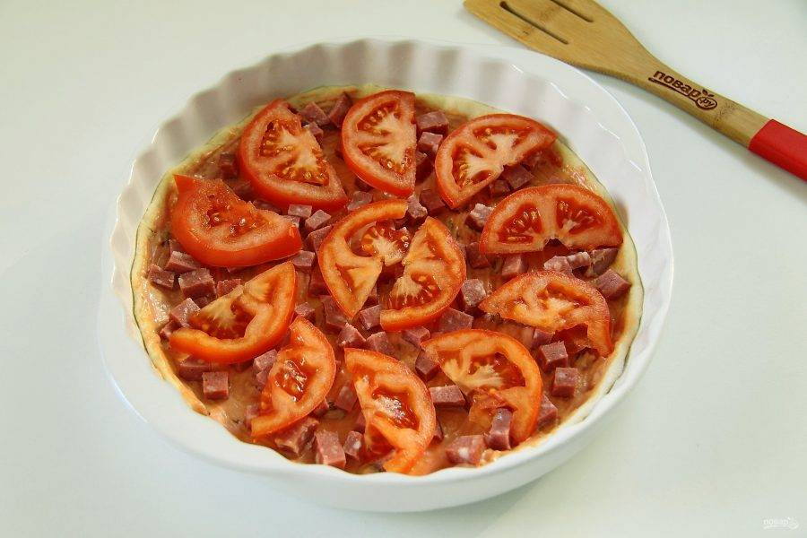 На колбасу положите нарезанный дольками помидор.