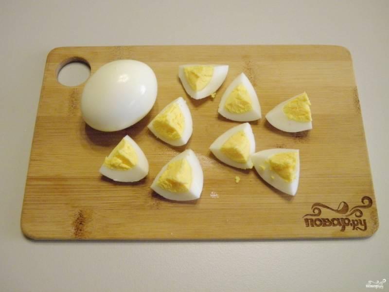 Вареные яйца порежьте на 8 частей каждое.