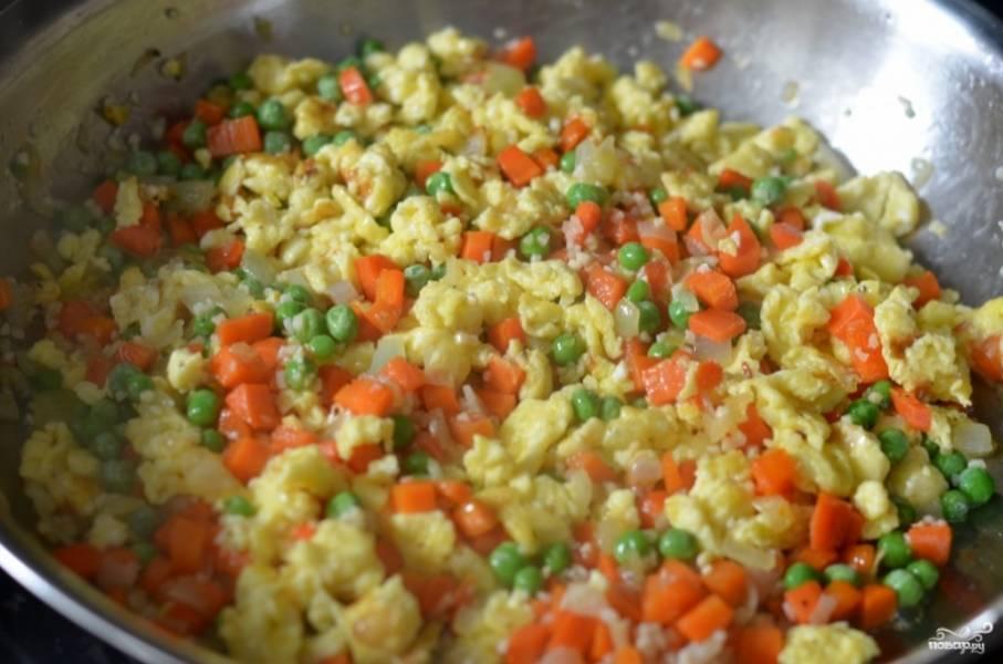 3. Через пару минут можно добавить щепотку соли (при желании можно и перец) и активно все перемешать. Выложите на сковороду также зеленый горошек. Оставьте жариться еще около 3-5 минут.