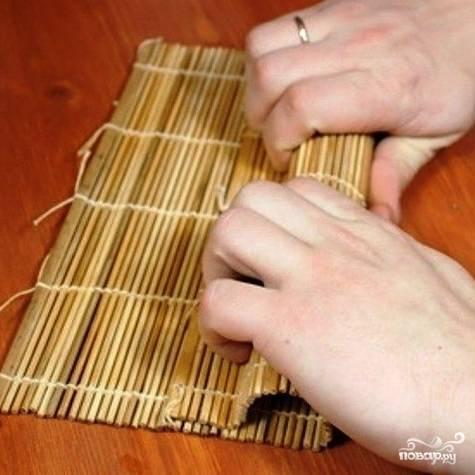Заворачиваем до самого конца бамбукового коврика, пару раз прокатываем получившуюся колбаску, чтобы листы нори скрепились.