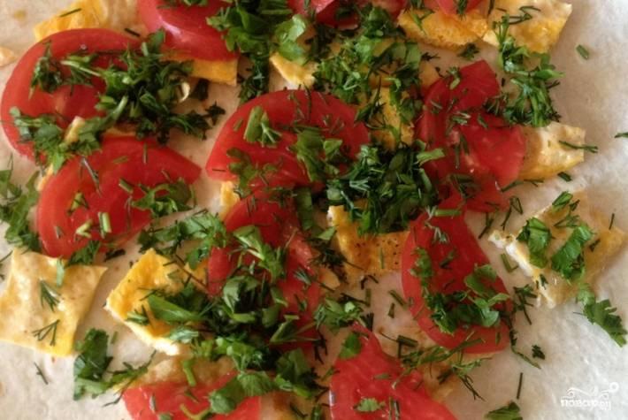 Сверху выкладываем порезанный томат и мелко нарезанную зелень. Сворачиваем лаваш конвертиком.