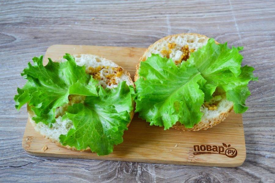 Начинаем собирать наши сэндвичи. Булочки разрежьте вдоль пополам. Нижнюю часть смажьте 1 ч. ложки горчицы. Мне нравится дижонская горчица, но можно использовать мягкую американскую или острую. Сверху положите по несколько листьев салата (это по вкусу).