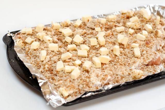 5. Сверху присыпать измельченными панировочными сухарями, а чтобы получилась вкусная корочка сверху выложить небольшие кусочки сливочного масла. Для аппетитной корочки можно использовать также тертый сыр, например.