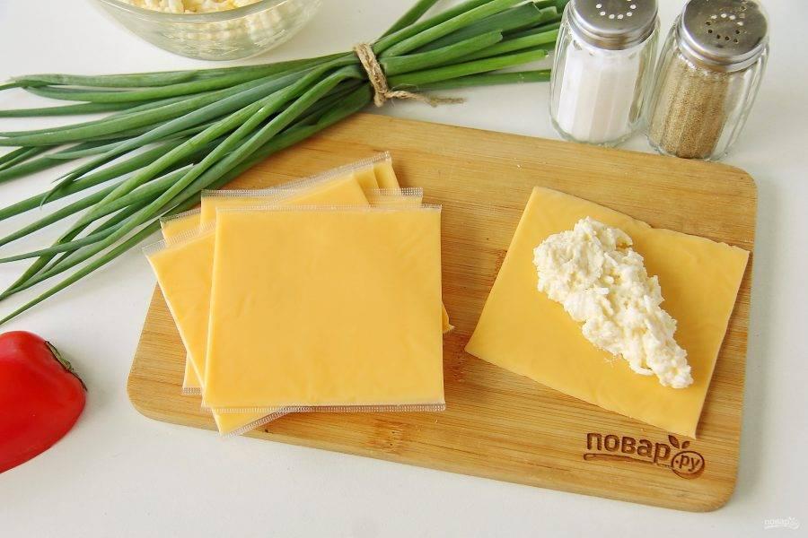 Освободите поочередно от пленки пластинки плавленого сыра. По центру положите яичную массу как на фото.