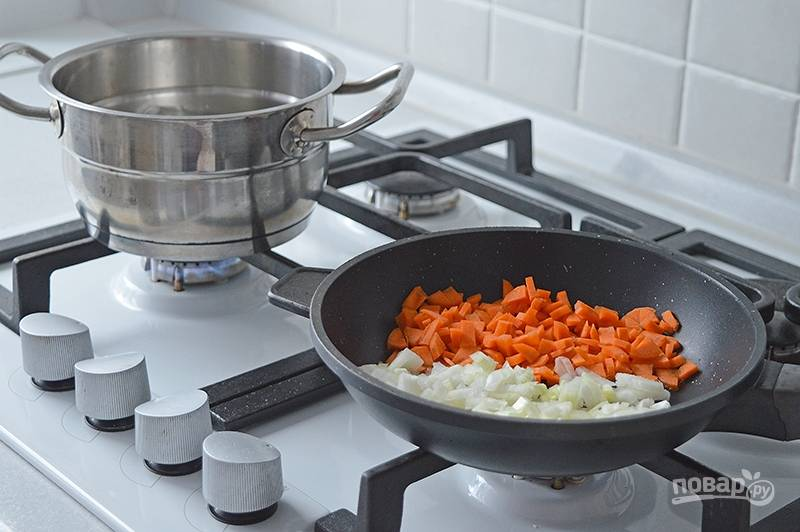 Опускаем картофель в кипящую подсоленную воду. Тем временем обжариваем на масле до золотистости лук и морковь. Перекладываем зажарку к картофелю и варим до готовности овощей.
