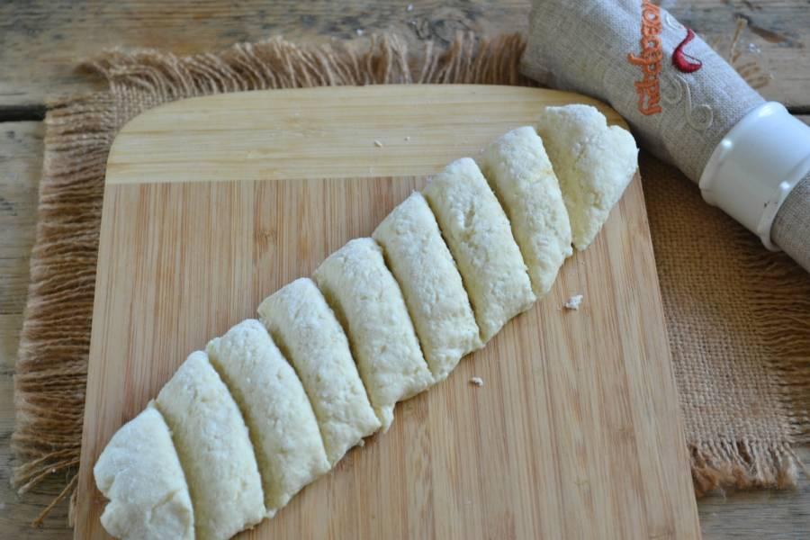 Раскатайте тесто в длинную колбаску, порежьте его на кусочки небольшого размера.