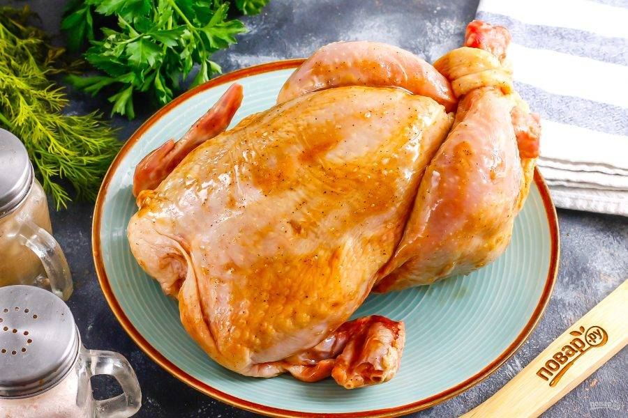 Сделайте надрезы в коже возле гузки и вставьте в нее ножки птицы крест-накрест.