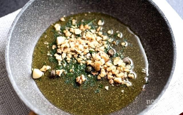 2.В кастрюле с кипящей подсоленной водой отварите спагетти согласно инструкции на упаковке. Пока спагетти варятся, в сковороде с горячим оливковым маслом слегка обжарьте нарезанный чеснок и каперсы. Выключите плиту, добавьте нарезанную петрушку, орехи и перемешайте.