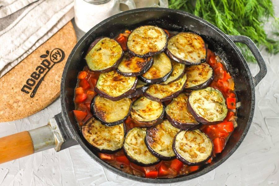 Выложите в томатную массу обжаренные баклажаны и потушите все содержимое емкости еще 3-4 минуты.