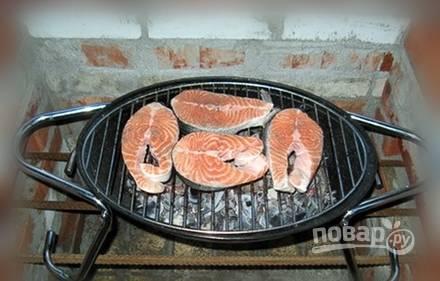 Выложите решётку на угли и готовьте рыбу около 20 минут.