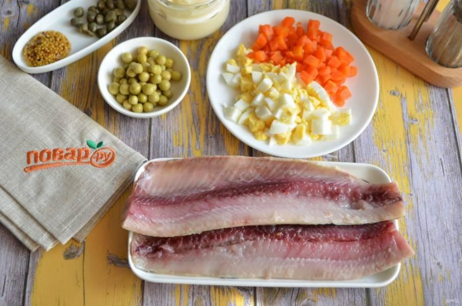 2. Подготовьте селедочное филе: снимите его с хребта, удалите кожу, косточки. Очистите яйцо и морковь, порубите мелко кубиками.