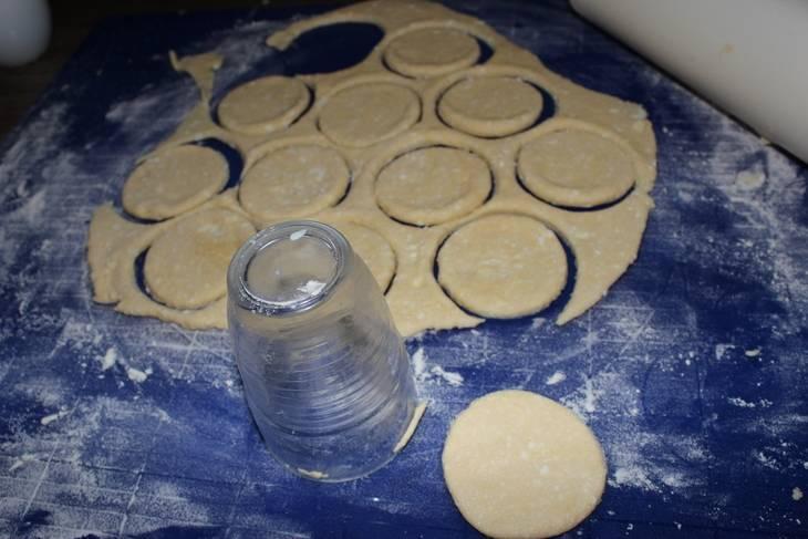 После этого присыпьте поверхность мукой. Раскатайте на ней половину теста шириной в 0,5 см. Вырежьте заготовки с помощью стакана.