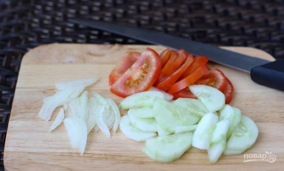 Лук очистите и вымойте вместе с огурцами и помидорами. Затем обрежьте у огурца кончики с обеих сторон, очистите его от кожицы и нарежьте половинками кружочков. Так же порежьте томаты и репчатый лук.