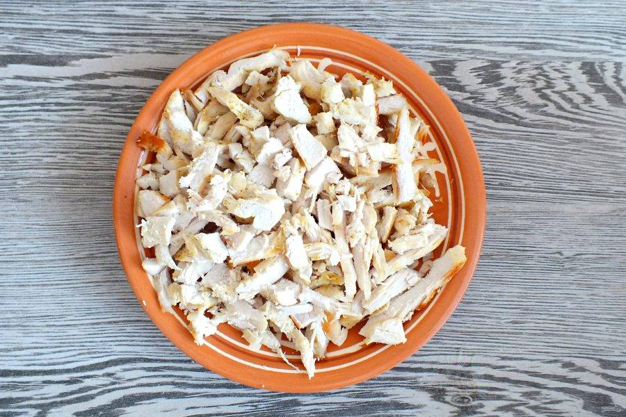 Обжаренное куриное филе разберите на волокна или нарежьте соломкой.