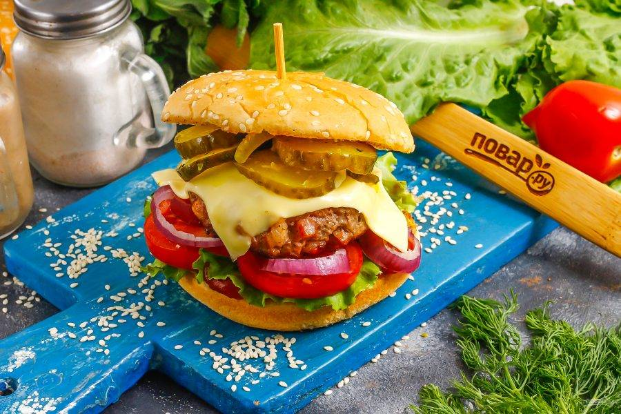 Накройте сверху бургер второй половинкой булочки и закрепите шпажкой. Приятного аппетита!