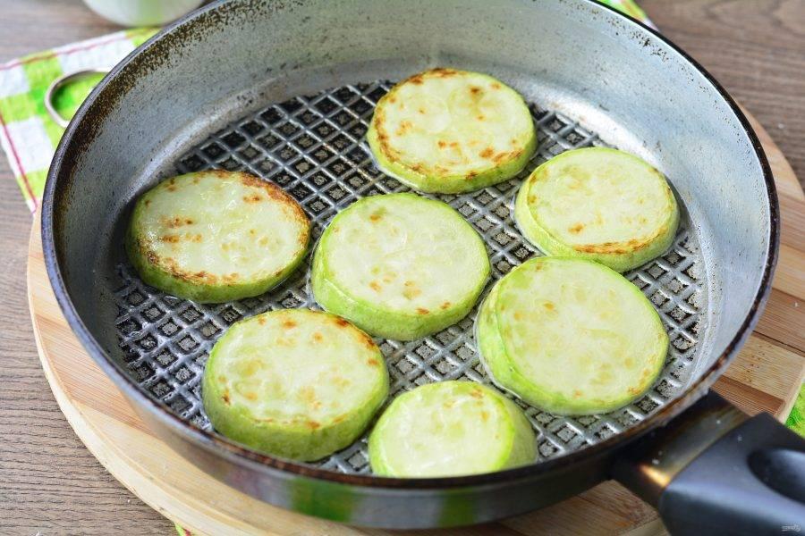 Отдельно обжаривайте овощи. Сперва кабачки. Разогрейте масло в сковороде, выложите кабачки, обжаривайте на небольшом огне с двух сторон 3-4 минуты, посолите по вкусу.