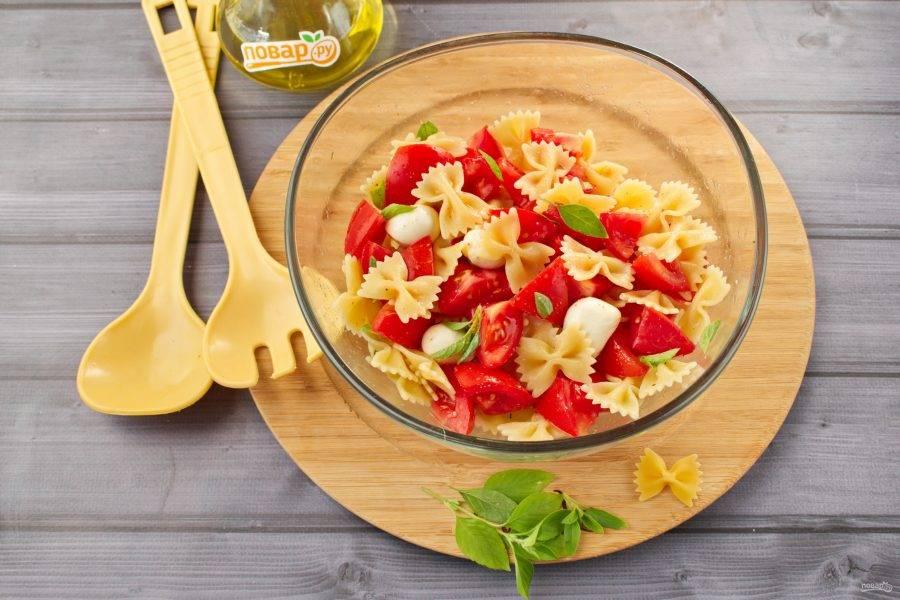 В салатнике соедините пасту Фарфалле, томаты, базилик, моцареллу-бэби, итальянские травы, перемешайте. Посолите и поперчите по вкусу.