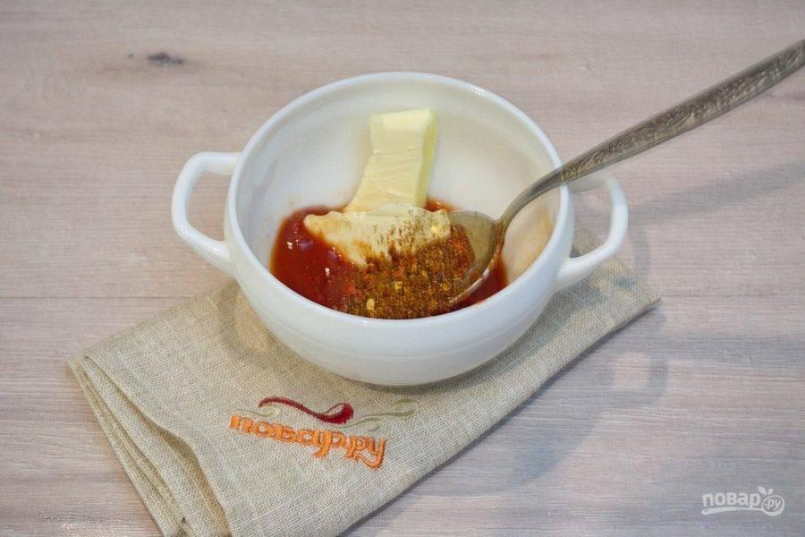 Пока крылья жарятся, смешайте томатную пасту, сливочное масло, специи, выдавленный через пресс чесночок и немного воды. Поставьте в микроволновку и растопите. Перемешайте.