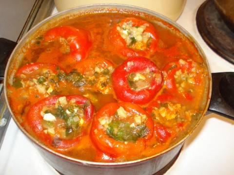 3. Отдельно обжариваем лук и морковь, добавляем томатную пасту и заливаем двумя стаканами воды. Доводим до кипения и заливаем пассировкой наш перец в глубокой емкости. После этого ставим на слабый огонь и тушим около часа.