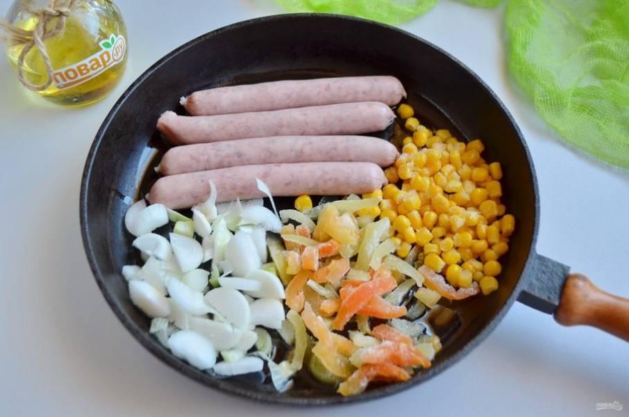 Разогрейте растительное масло на сковороде, положите сразу колбаски, овощи и обжарьте до золотистой корочки.
