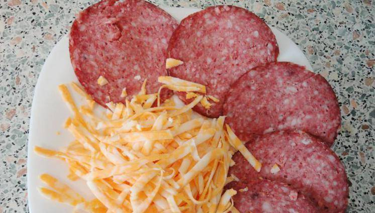 3. Затем выкладываем колбасу и сыр. Колбасу сразу нарезаем кольцами, после чего можно сделать нарезку соломкой. Сыр распределяем по всей поверхности.