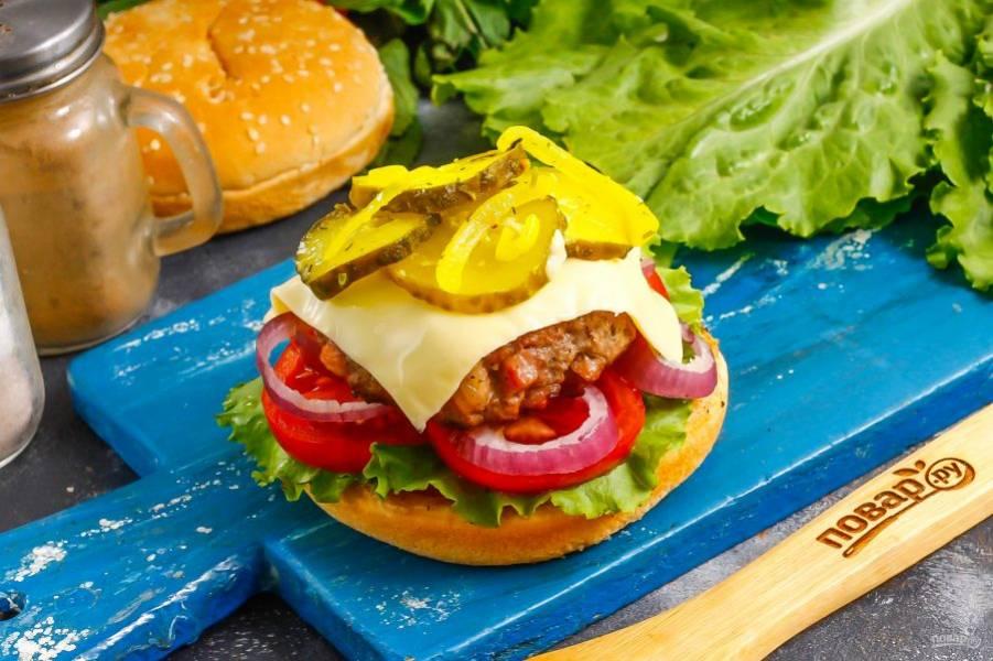 На котлету выложите тостовый сыр, а на него — маринованные огурцы. Сыр сам расплавится на горячей котлете и вам не нужно будет подогревать бургер в микроволновке.