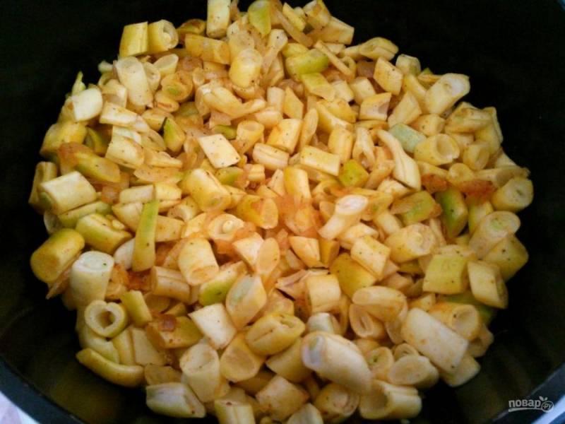 Добавьте к луку специи и готовьте ещё примерно минуту, а затем влейте воду и добавьте стручковую фасоль, нарезанную небольшими кусочками.