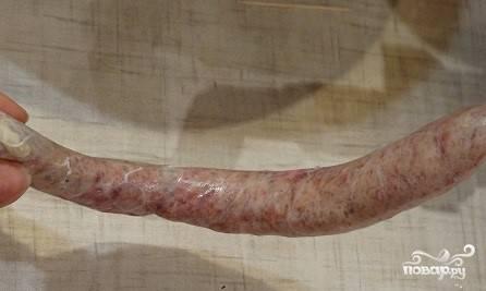 5. Заложите в мясорубку фарш. Набейте с его помощью череву. Получится длинная колбаса. Ее следует перевязать на более маленькие части.