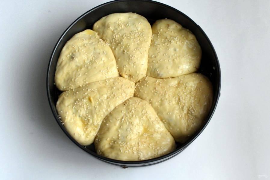 Уложите пирожки в форму и смажьте яйцом с молоком. Посыпьте кунжутом и дайте расстояться минут 20.