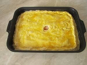 5. Почти готово! Сейчас накройте все слои пирога оставшимся тестом, предварительно тоже раскатанным, смажьте пирог сырым яйцом (здесь нужно немного взбить его, чтобы смешать желток и белок в однородную массу), можно воспользоваться кулинарной кисточкой. Важный момент: в центре пирога сделайте небольшое отверстие, тогда все ингредиенты хорошо пропекутся!