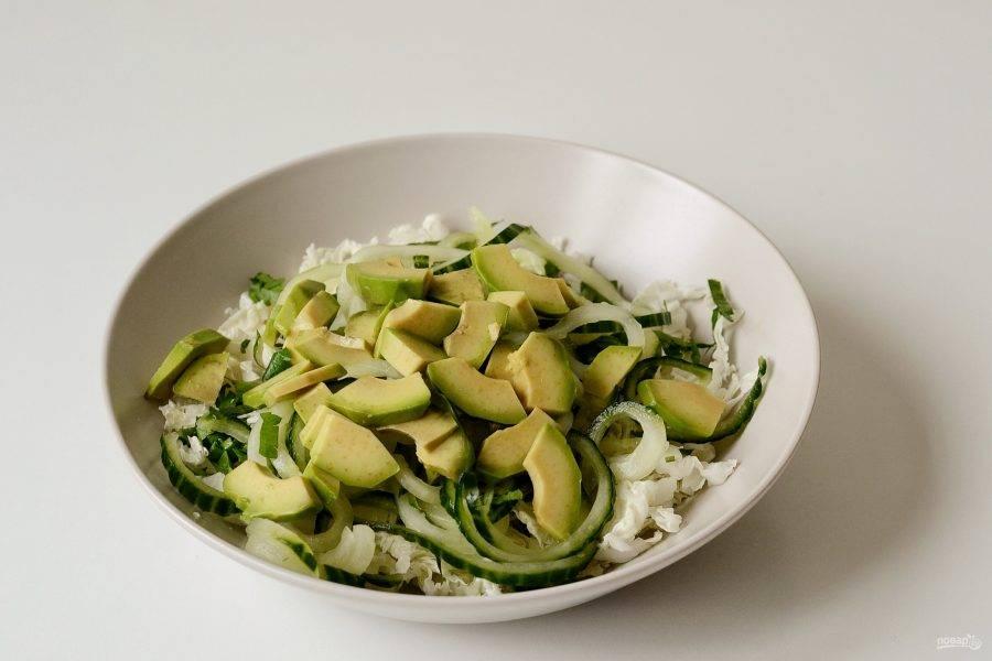 Авокадо очистите от кожуры, удалите косточку и нарежьте  дольками.