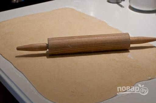 Готовое тесто раскатываем на большой поверхности, посыпанной мукой, в тонкий пласт.