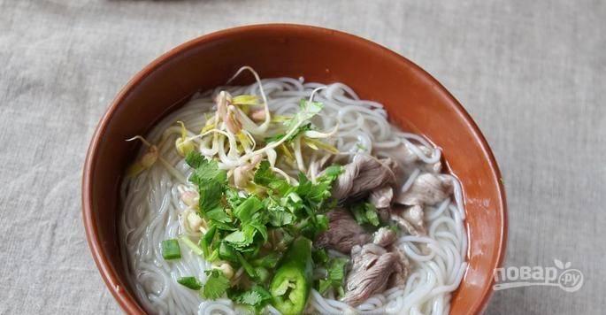 Влейте в пиалку с мясом и лапшой горячий суп. Дайте ему слегка остыть, присыпьте сверху зеленым луком с петрушкой и положите острый перец.