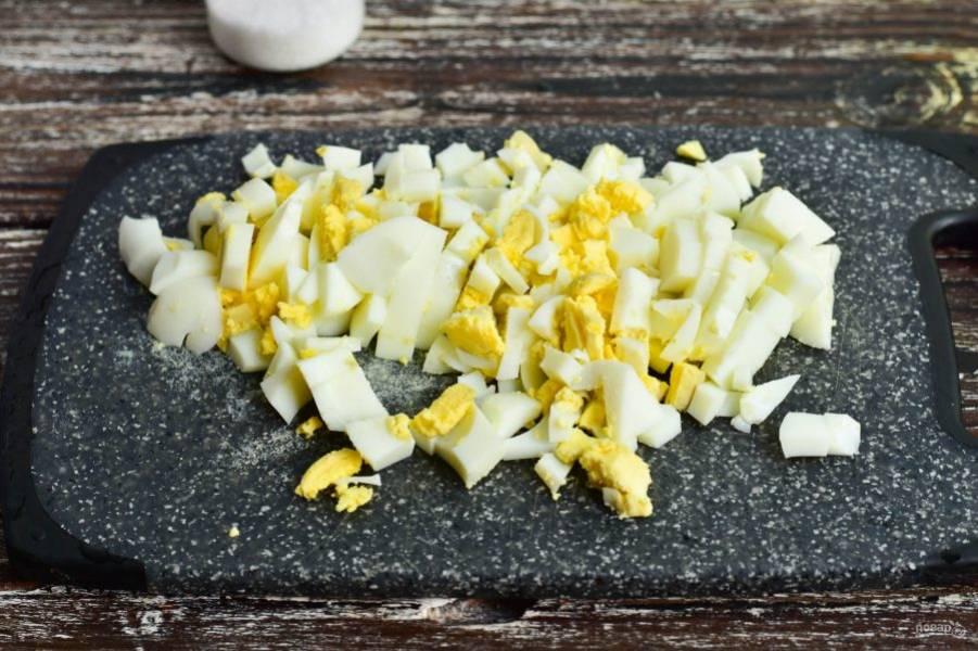 Нарежьте вареные куриные яйца.