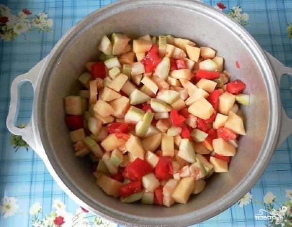 3. Подготовьте ингредиенты для овощной части рагу. Для этого очистите кабачок и картошку. Нарежьте оба овоща кубиками. Выложите в казанок. Вначале кабачки, а сверху – картофель. Помойте томаты. Затем ошпарьте их кипятком и снимите с них кожицу. Нарежьте их кубиками и выложите в казанок к остальным компонентам. Все перемешайте.