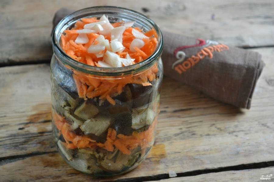 Складывайте в банки овощи слоями. Сначала — запеченные баклажаны, затем — морковь и чеснок, потом снова выкладываем баклажаны и снова морковь с чесноком.