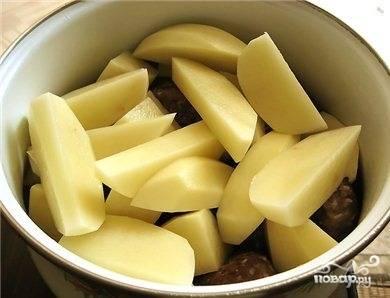 Готовые тефтели кладем в глубокую кастрюлю. Сверху укладываем крупно нарезанный картофель.