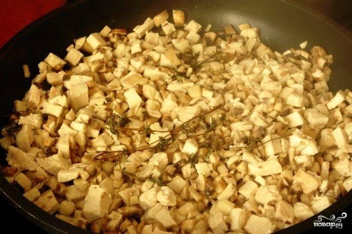 Теперь в той же сковороде растапливаем сливочное масло, добавляем курицу, шампиньоны и веточку тимьяна. Помешивая, обжариваем до готовности грибов. Масса должна уменьшиться примерно в 3 раза в объеме - шампиньоны сильно ужариваются.