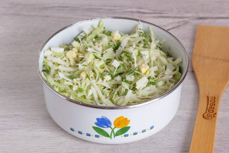 Помойте молодую капусту и зелень. Капусту мелко нашинкуйте, зелень и очищенные яйца порубите. Всё хорошо перемешайте и посолите по вкусу.