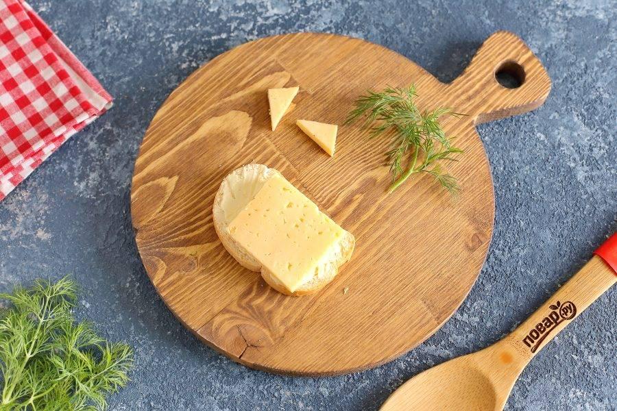 Второй бутерброд будет в виде веселого мышонка. Для этого часть сыра нарежьте в виде двух треугольников и отложите пока в сторону. Оставшийся кусочек выложите поверх батона.