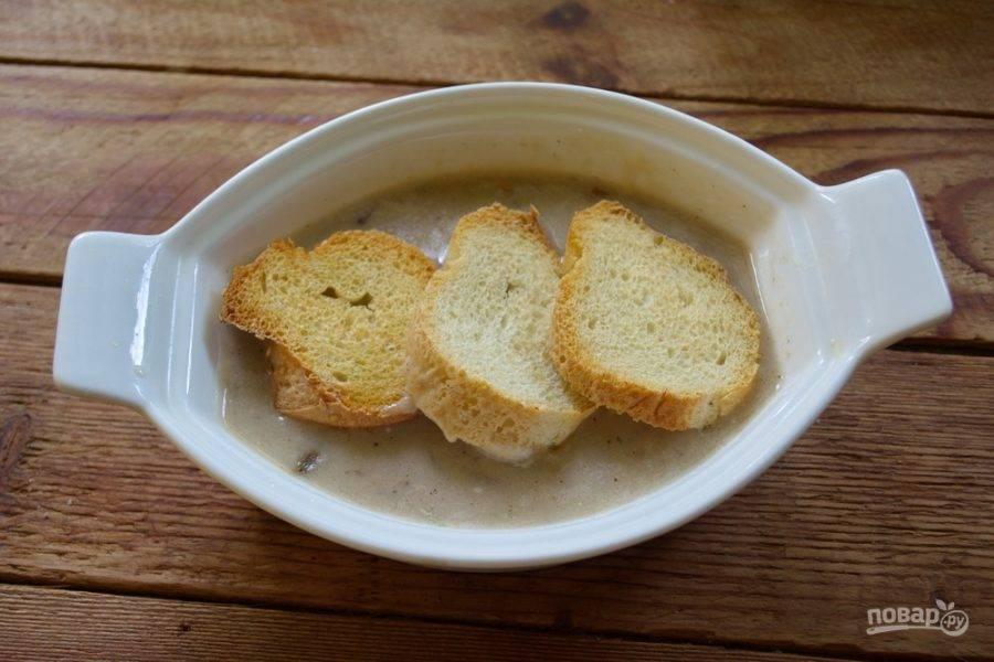 В форму с супом уложите подрумяненные кусочки хлеба.