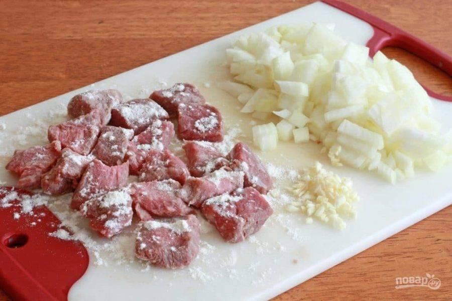 1.Вымойте говядину и нарежьте ее небольшими кубиками. Очистите лук и нарежьте его кусочками среднего размера, измельчите чеснок. Посыпьте мясо 1 столовой ложкой муки.