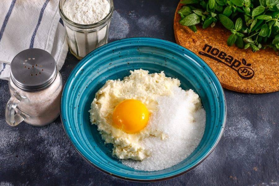 Творог выложите в глубокую емкость, разделите куриное яйцо на белок и желток, желток добавьте в емкость, а белок взбейте миксером, всыпьте к творогу соль и сахар. По желанию можно добавить ванильный сахар или другой ароматизатор.